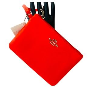 Coach NWT wristlet bag. Coral color. Strap tag